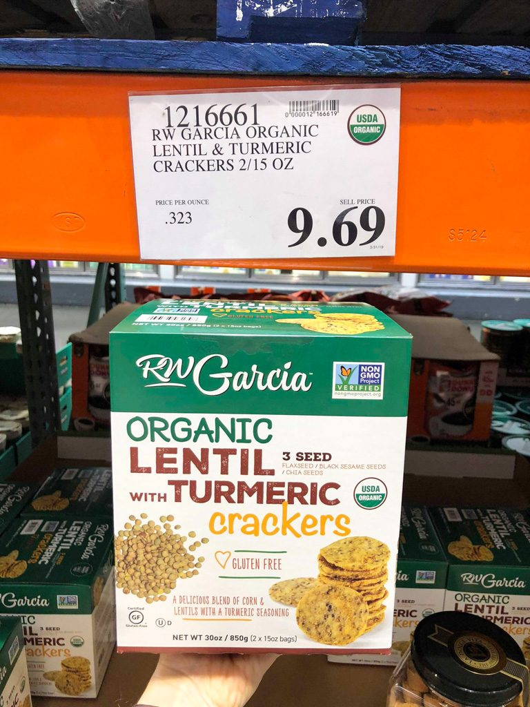 A hand holding a box of organic vegan RW Garcia lentil turmeric crackers for $9.69 at Costco.