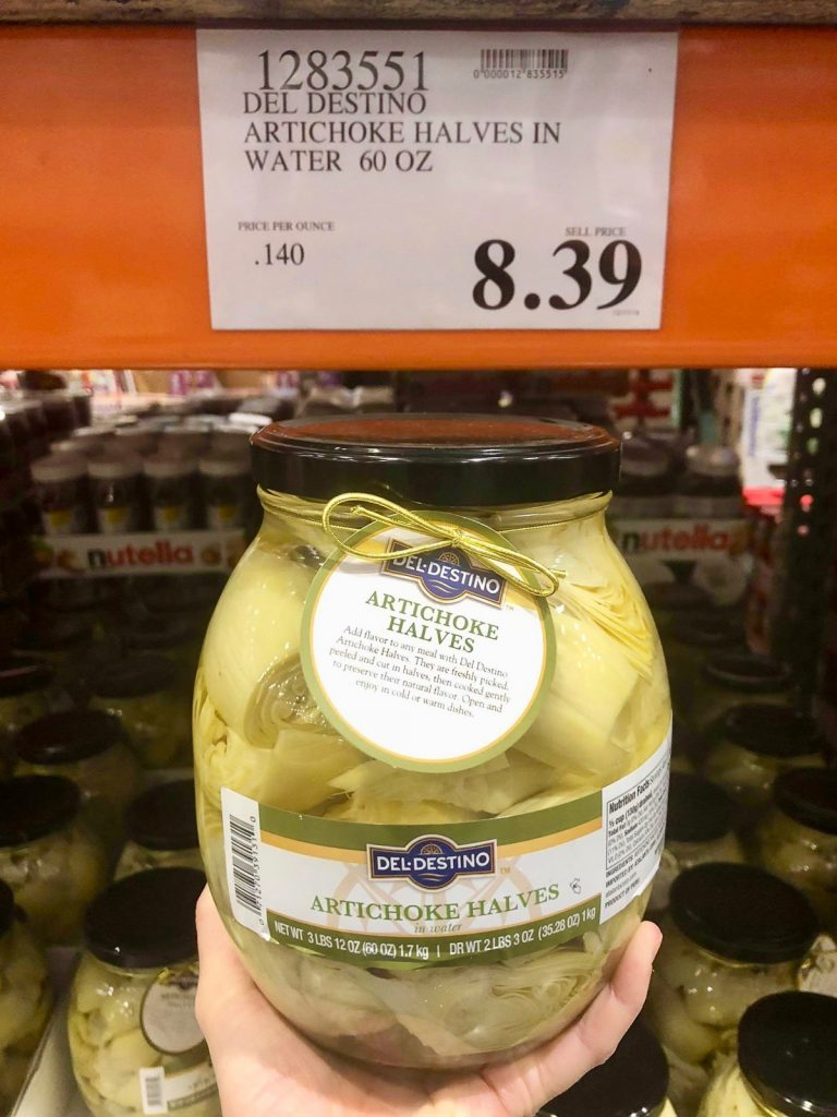 A hand holding a glass jar of vegan artichoke halves for $8.39 at Costco.