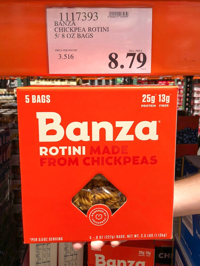 A hand holding a red box of vegan Banza pasta for $8.79 at Costco.