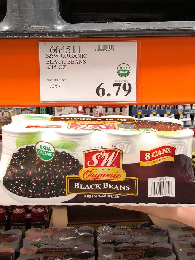 A hand holding an 8-pack of organic vegan canned black beans for $6.79 at Costco.