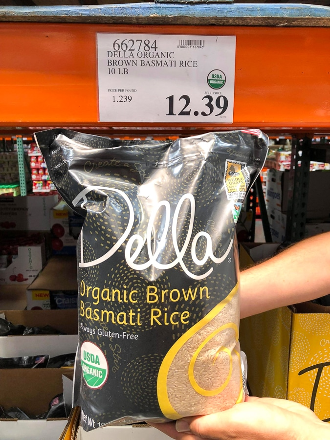 A hand holding a bag of organic vegan brown basmati rice for $12.39 at Costco.