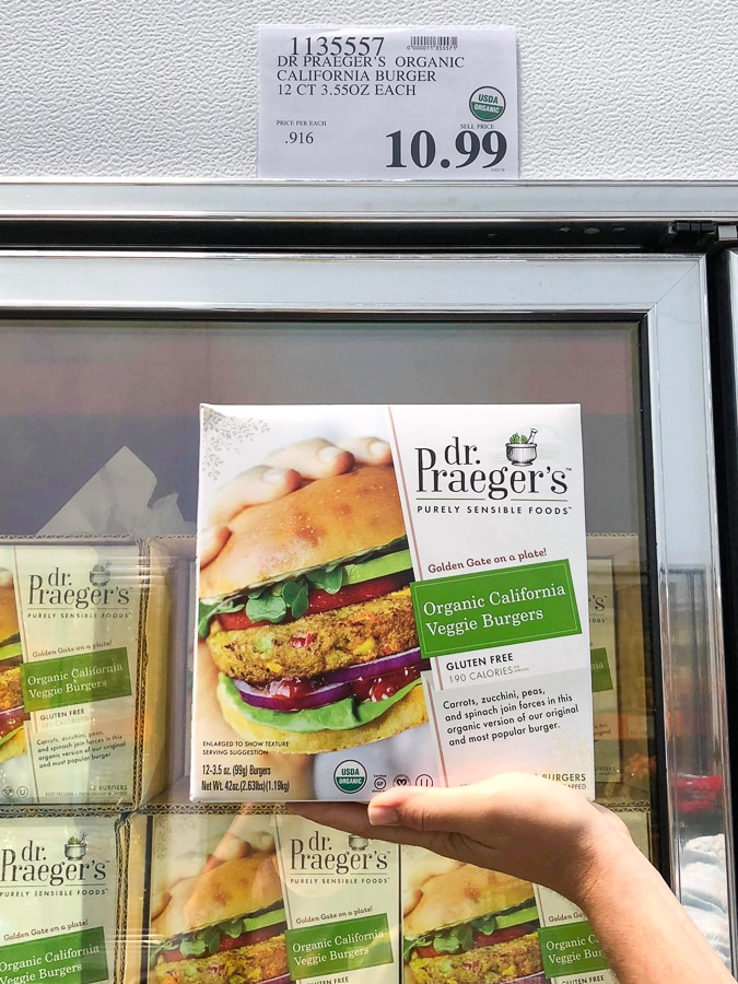 A hand holding a box of Dr. Praeger's organic vegan veggie burgers for $10.99 at Costco.