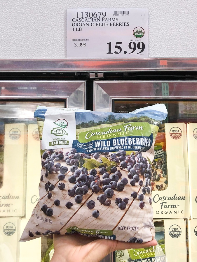 A hand holding a bag of organic frozen wild blueberries for $15.99 at Costco.