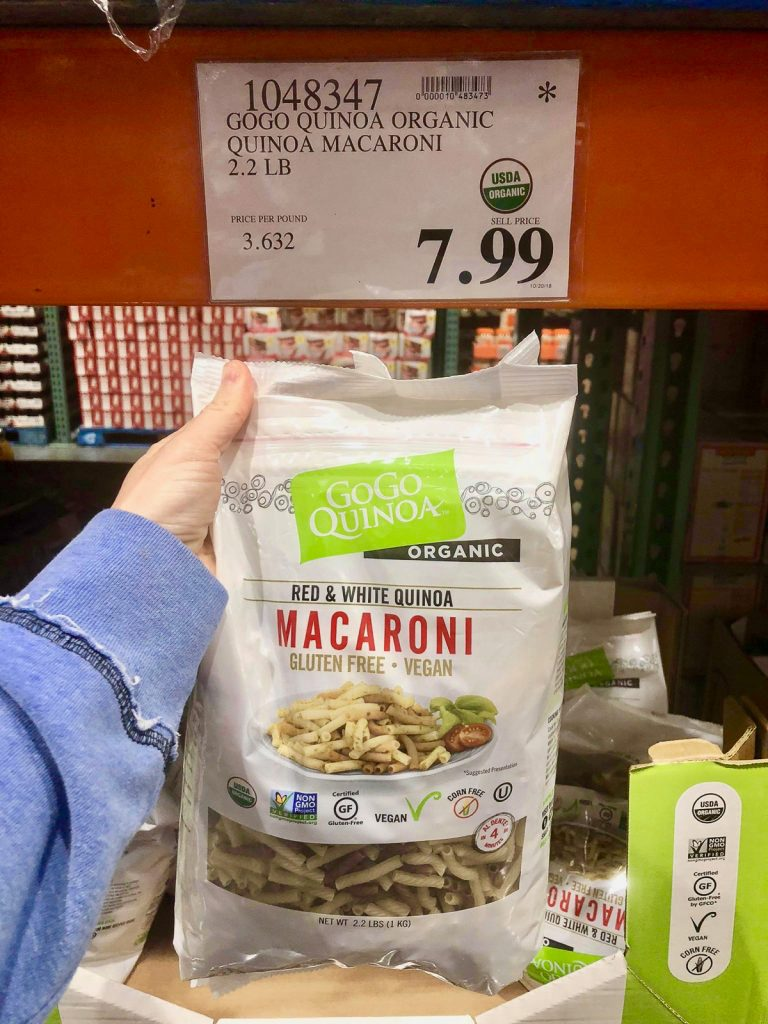 A hand holding a bag of GoGo Quinoa macaroni for $7.99 at Costco.