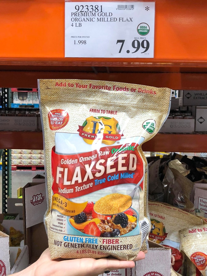 A hand holding a large bag of organic vegan flaxseed for $7.99 at Costco.