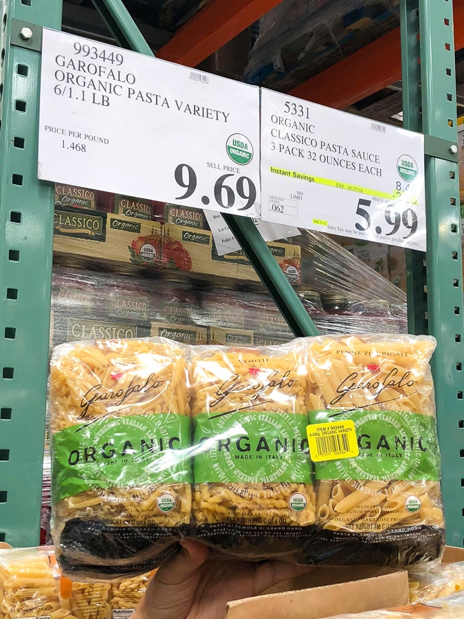 A hand holding a 6-pack of organic vegan pasta for $5.99 at Costco.
