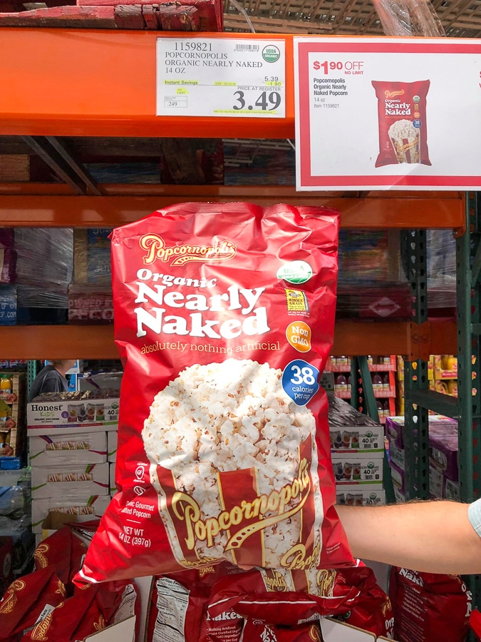 A hand holding a large red bag of organic vegan Popcornopolis popcorn for $3.49 at Costco..