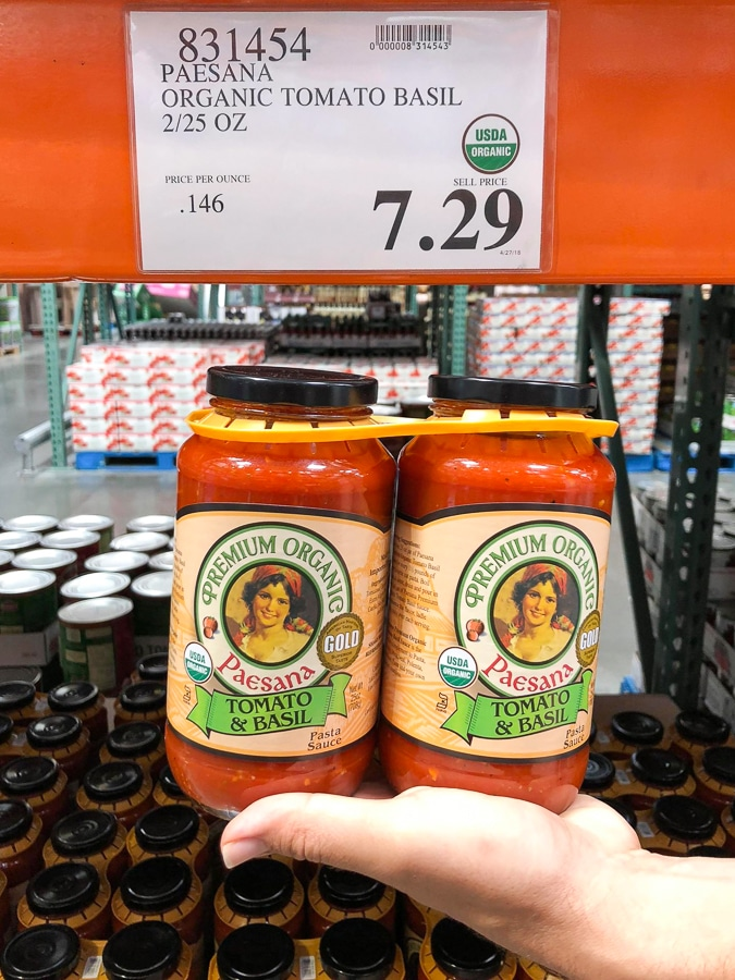 A hand holding a 2-pack of organic vegan tomato basil sauce in glass jars for $7.29 at Costco.