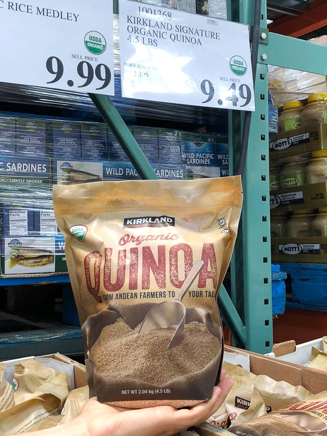 A hand holding a bag of organic vegan quinoa for $9.49 at Costco.