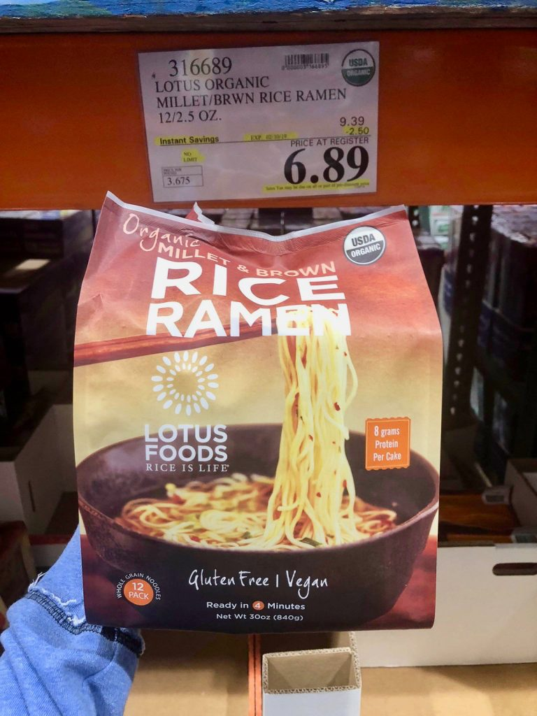 A hand holding a bag of organic vegan rice ramen noodles packets for $6.89 at Costco.