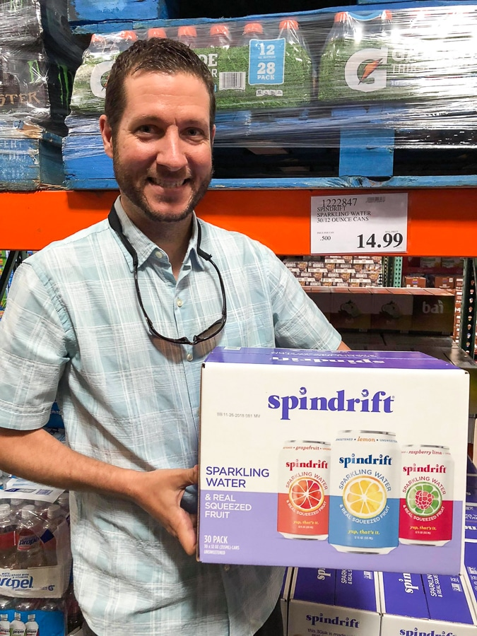A man holding a large box of Spindrift soda for $14.99 at Costco.