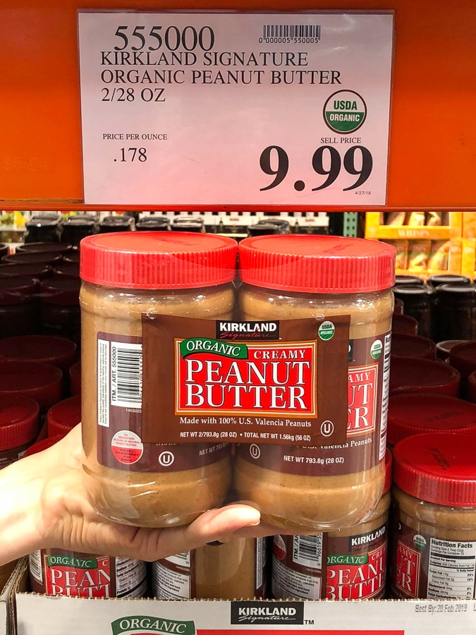 A hand holding a 2-pack container of organic vegan peanut butter for $9.99 at Costco.
