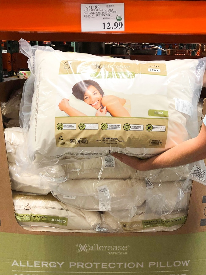 A hand holding an organic pillow for $12.99 at Costco.