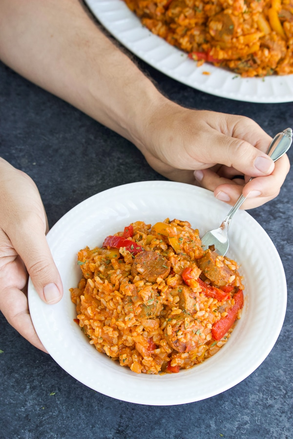 Two hands holding a white bowl full of vegan sausage and peppers with rice on a textured background.