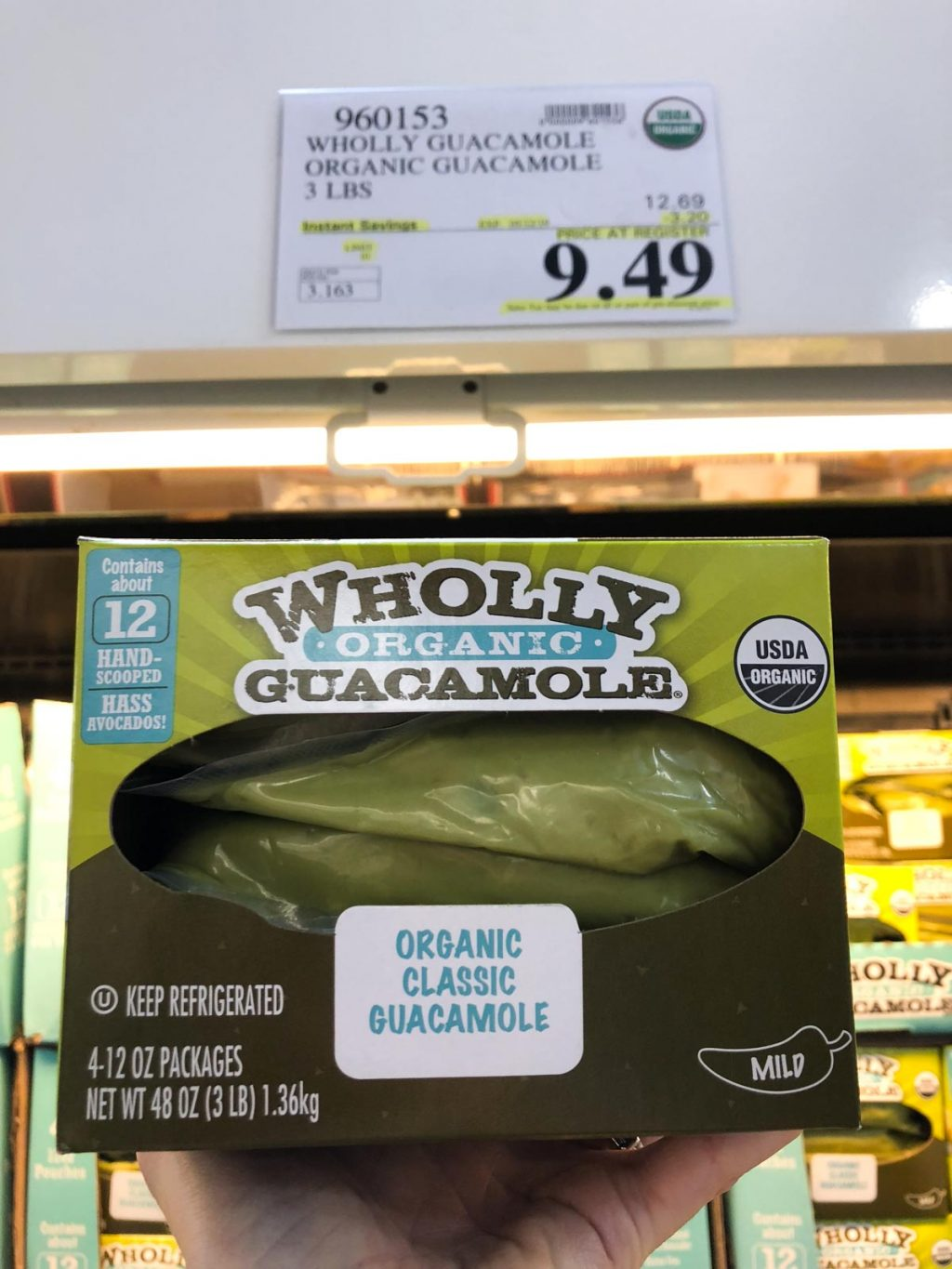 A hand holding a box of organic vegan Wholly Guacamole for $9.49 at Costco.