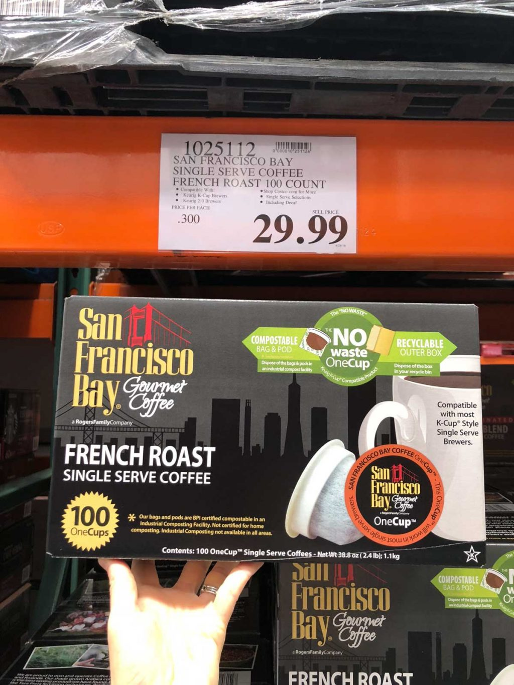A hand holding a large box of San Francisco Bay no waste cups for $29.99 at Costco.