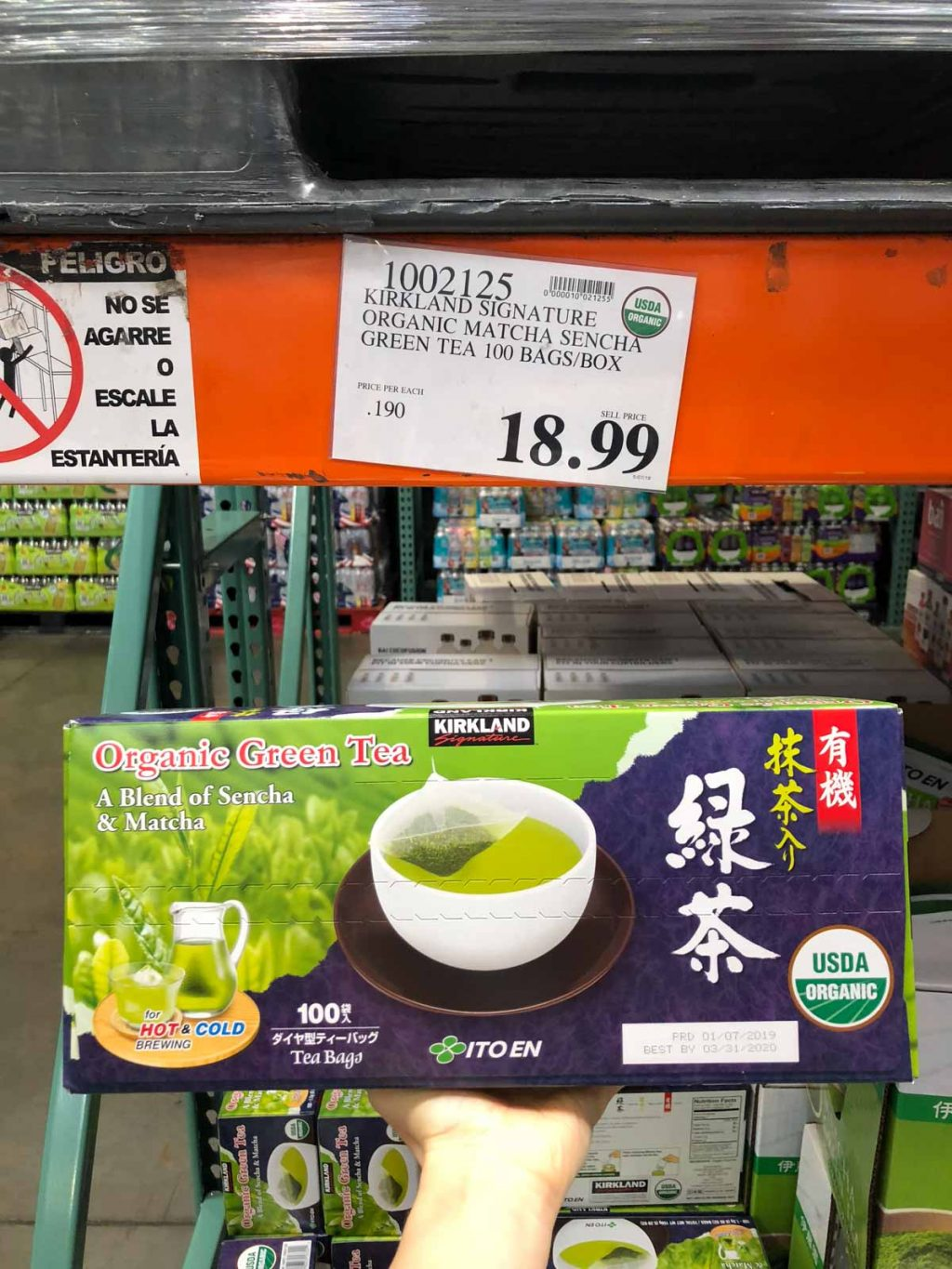 A hand holding a large box of organic green tea for $18.99 at Costco.