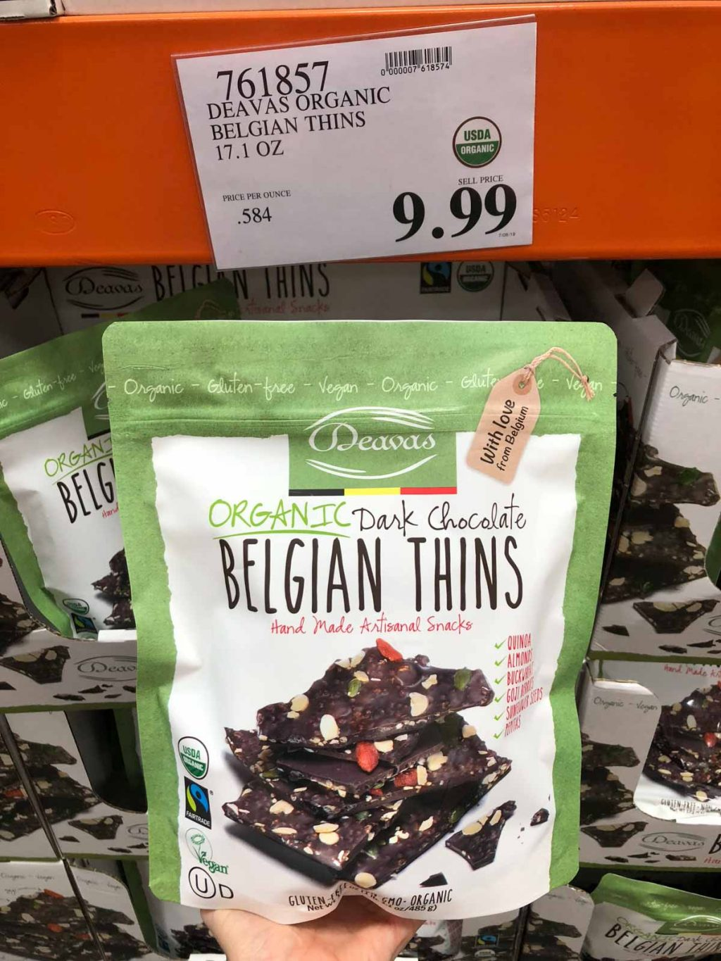 A hand holding a bag of organic vegan dark chocolate thins for $9.99 at Costco