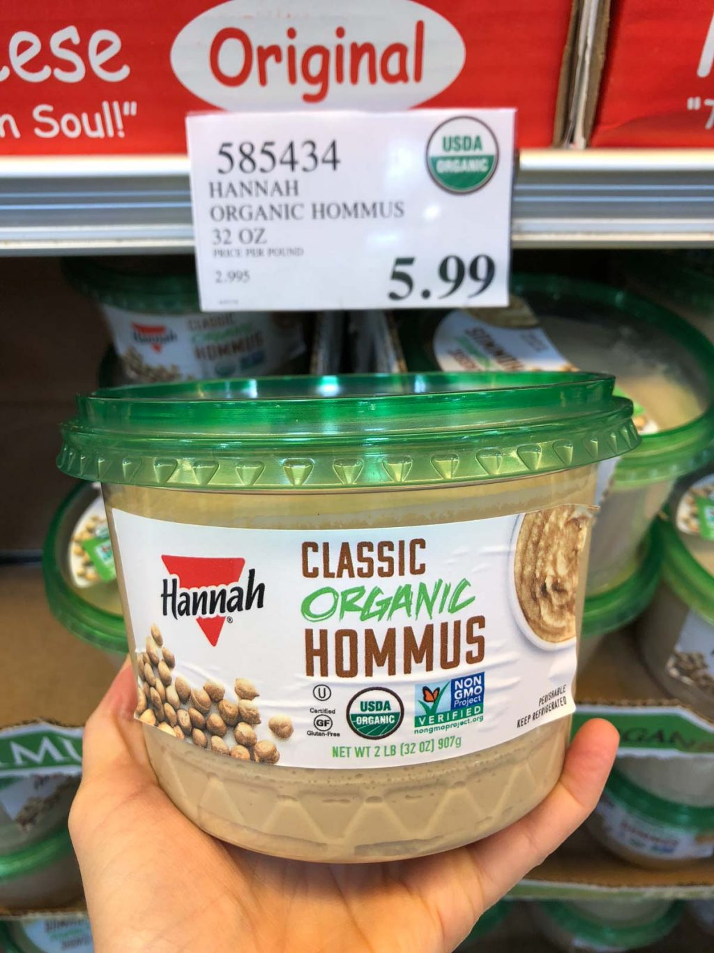 A hand holding a container of organic vegan hummus for $5.99 at Costco.
