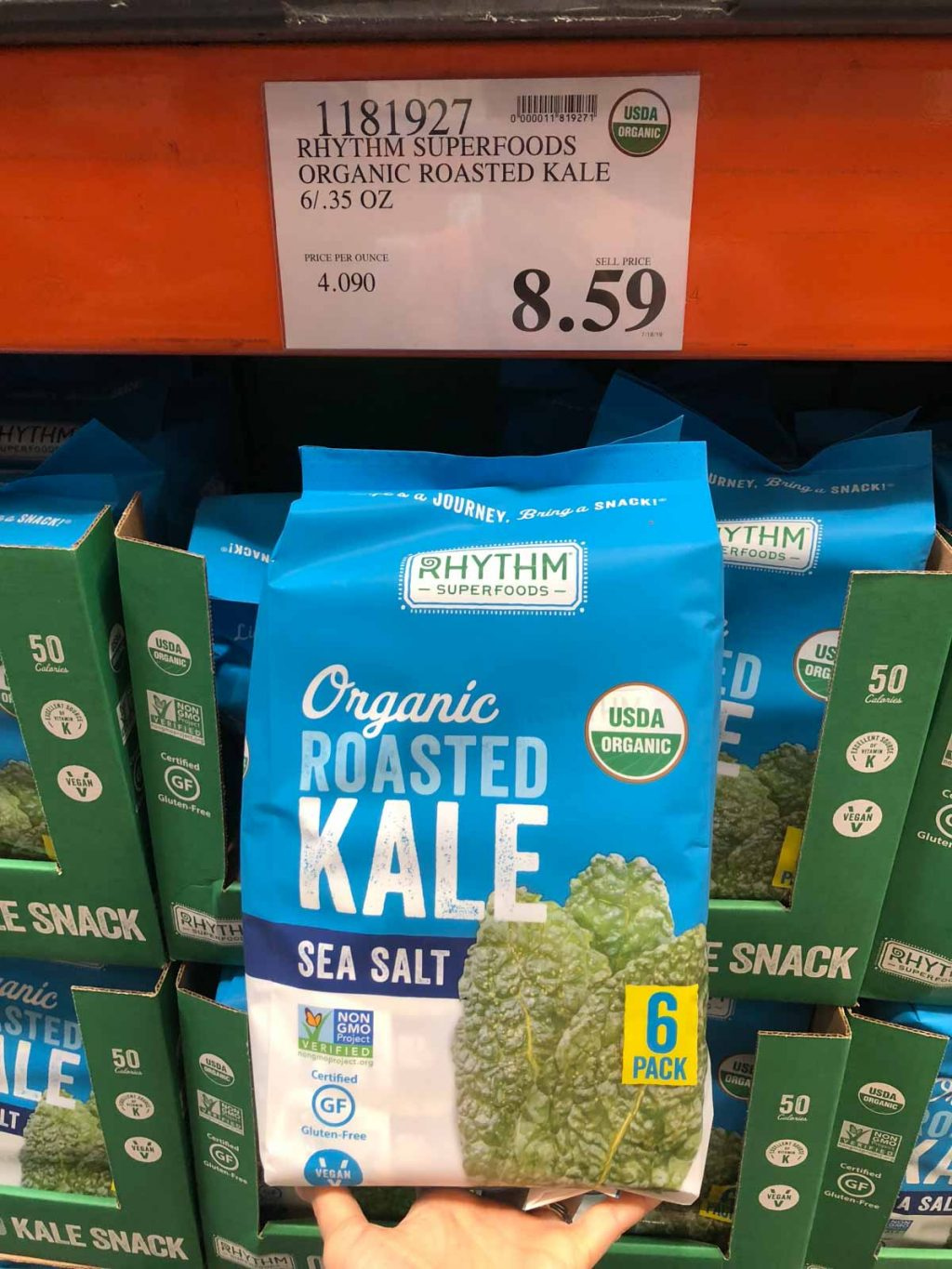 A hand holding a blue container of Rhythm organic vegan roasted kale snacks for $8.59 at Costco.