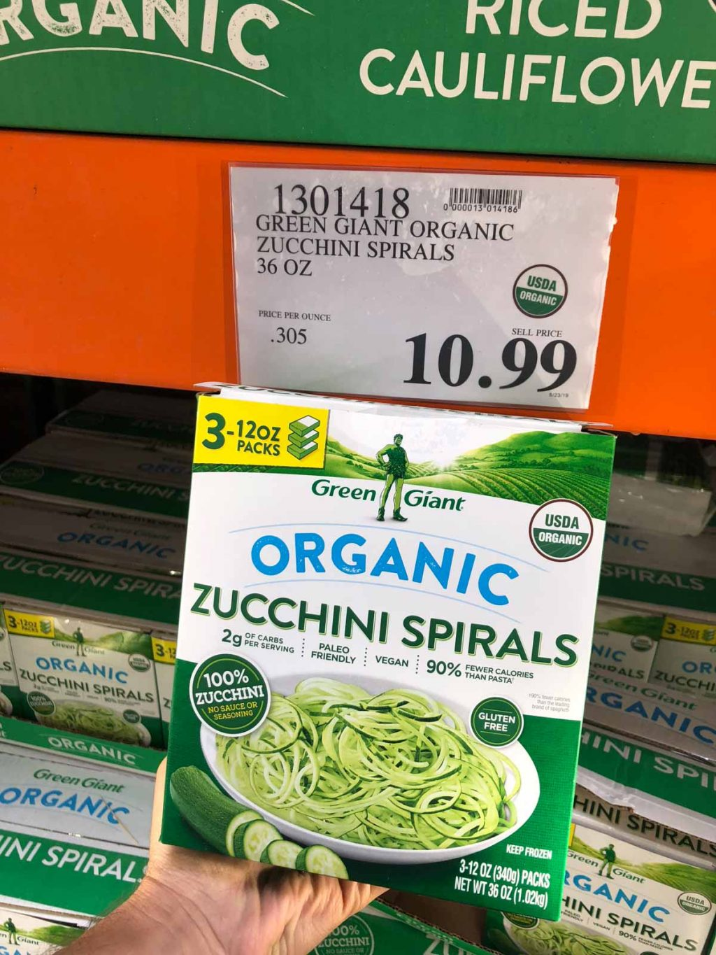 A hand holding a box of organic vegan frozen spirzelized zucchini noodles for $10.99 at Costco.