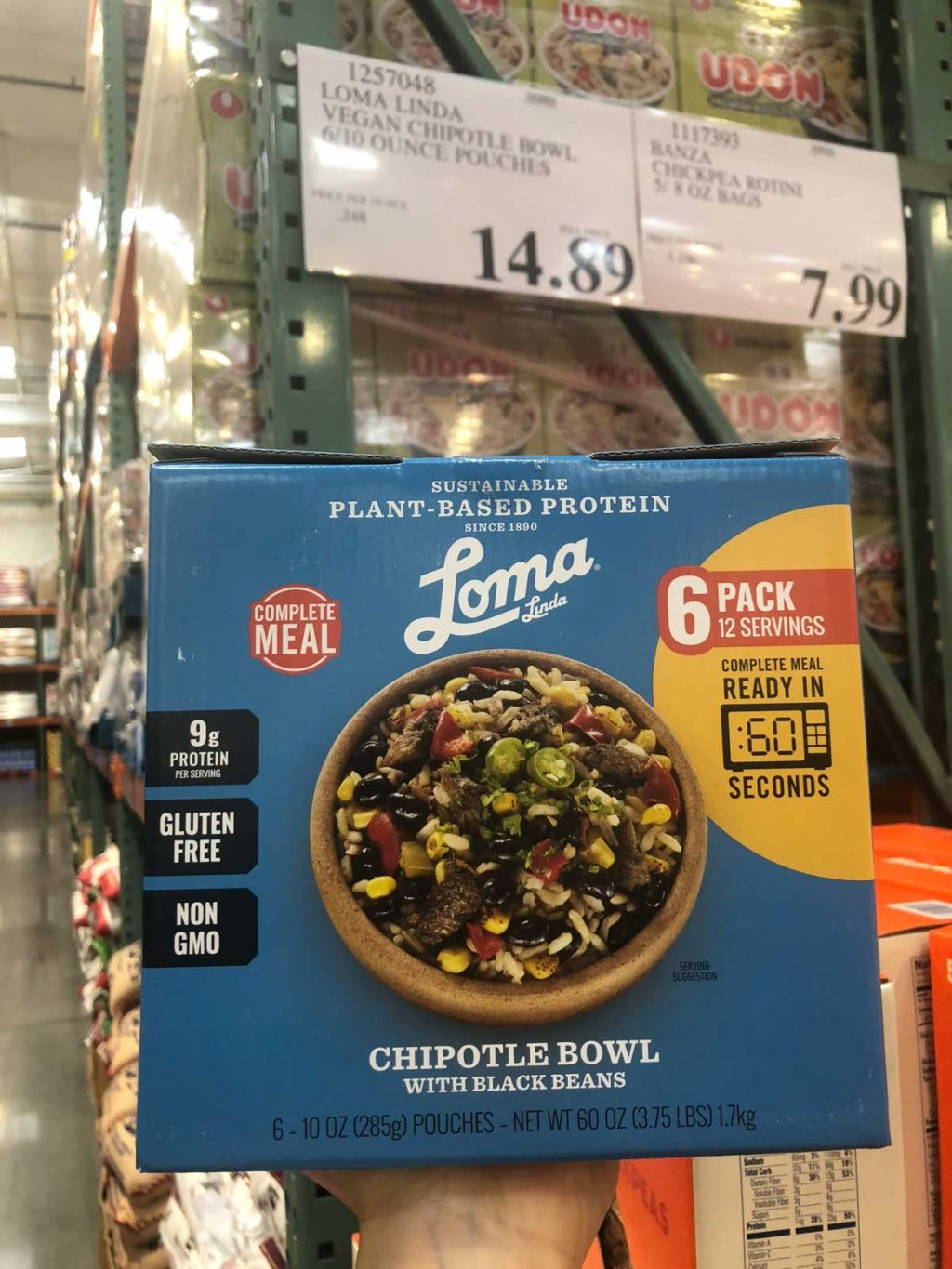 A hand holding a blue box of Loma Linda plant-based protein bowls for $14.89 at Costco.