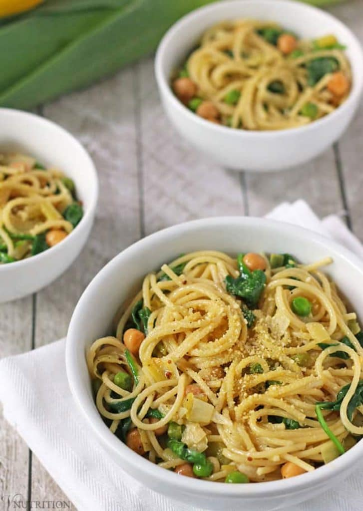 Three white bowls of lemon pasta with spinach and green peas on a grey background.