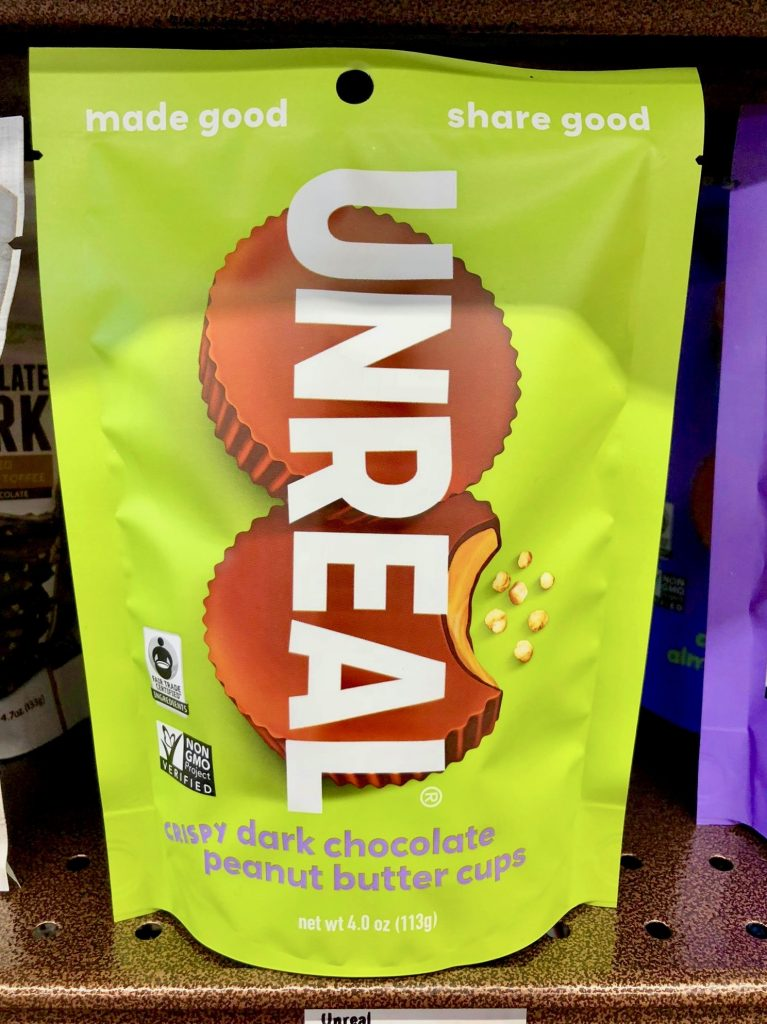 A green bag of Unreal dark chocolate peanut butter cups on a shelf.