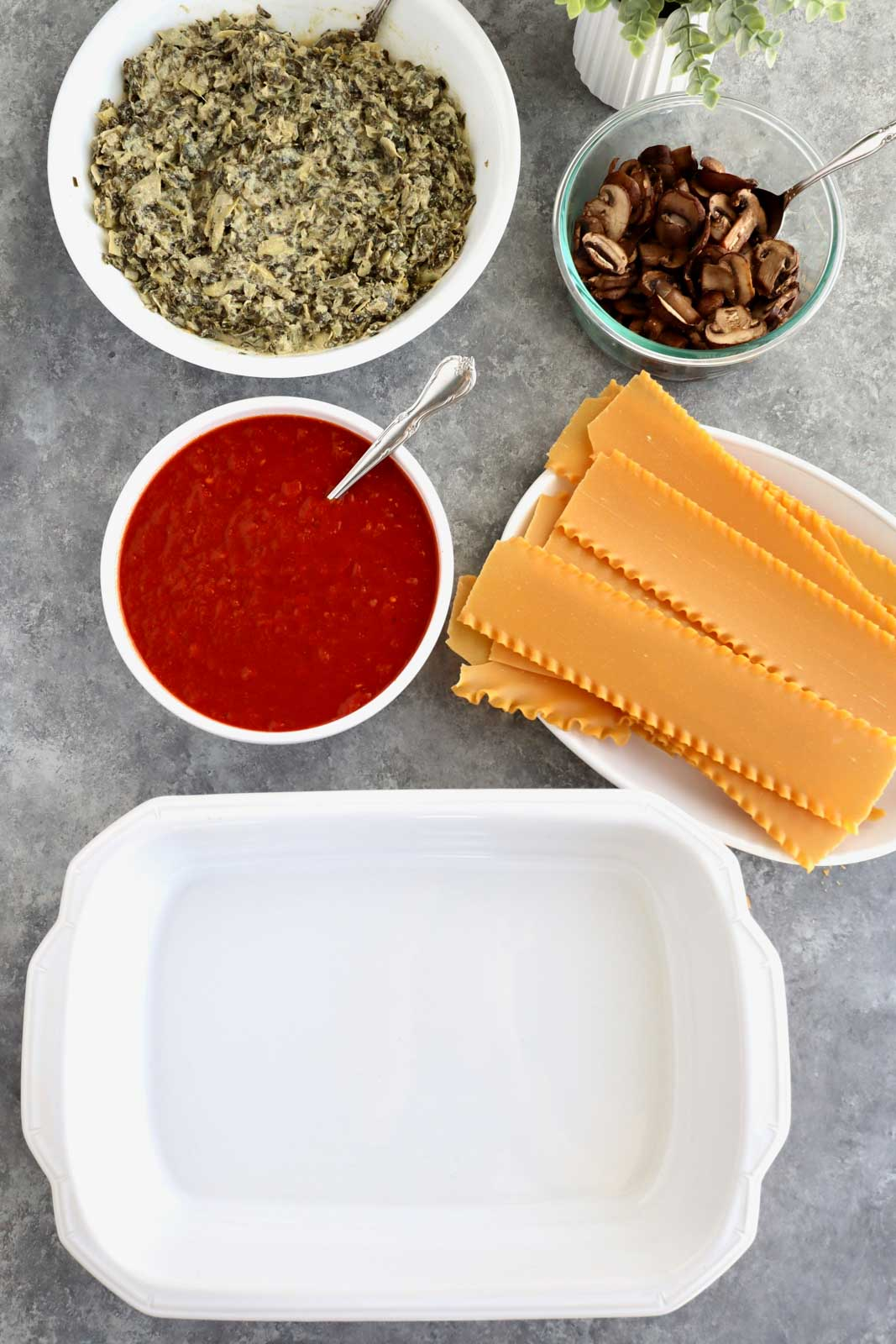 A white casserole dish, lasagna noodles, tomato sauce, mushrooms, and spinach dip in bowls.