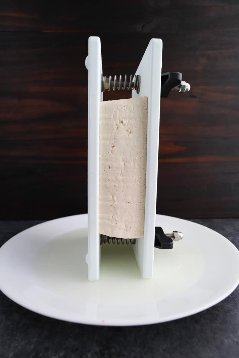 A block of tofu in a press being drained on top of a white plate on a dark background.