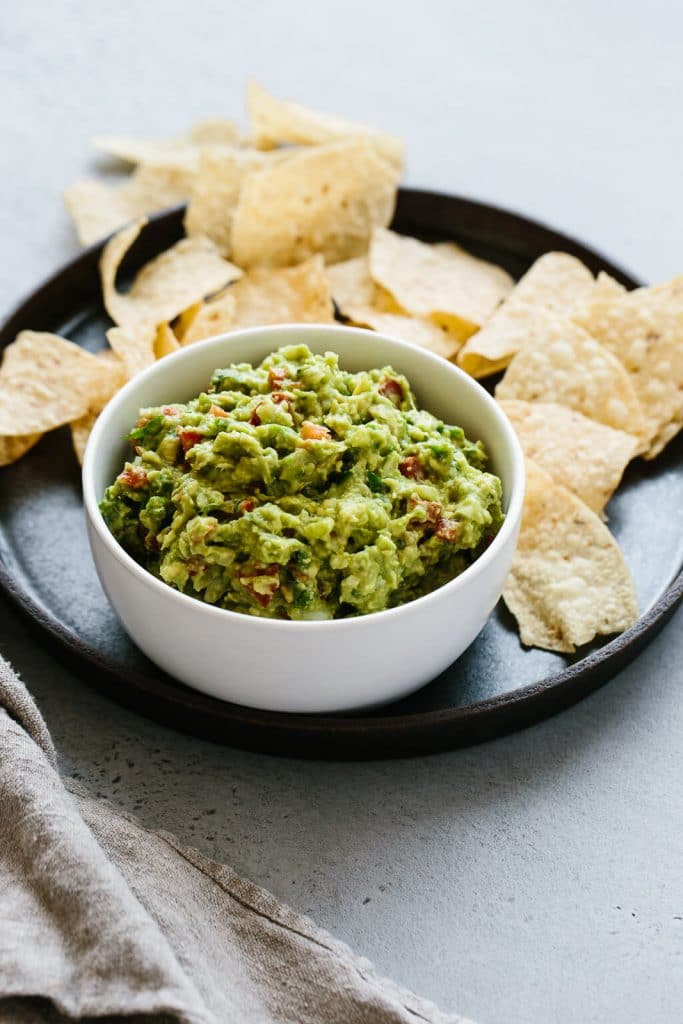 A small white bowl of vegan keto guacamole is on top of a matte black plate that is holding tortilla chips and it's resting on a neutral background..