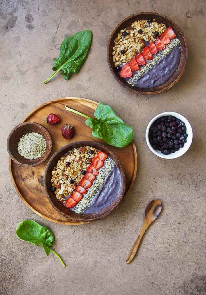 Two vegan keto breakfast blueberry smoothie bowls topped with hemp seeds, strawberries, and granola on a wooden platter that is resting on a neutral background.