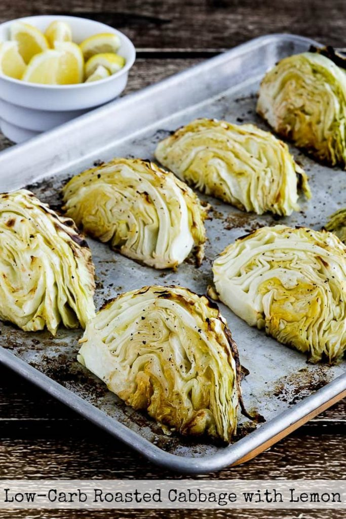 Low-carb vegan keto side dish of lemon roasted cabbage slices on a baking tray with a bowl of lemons on the side.