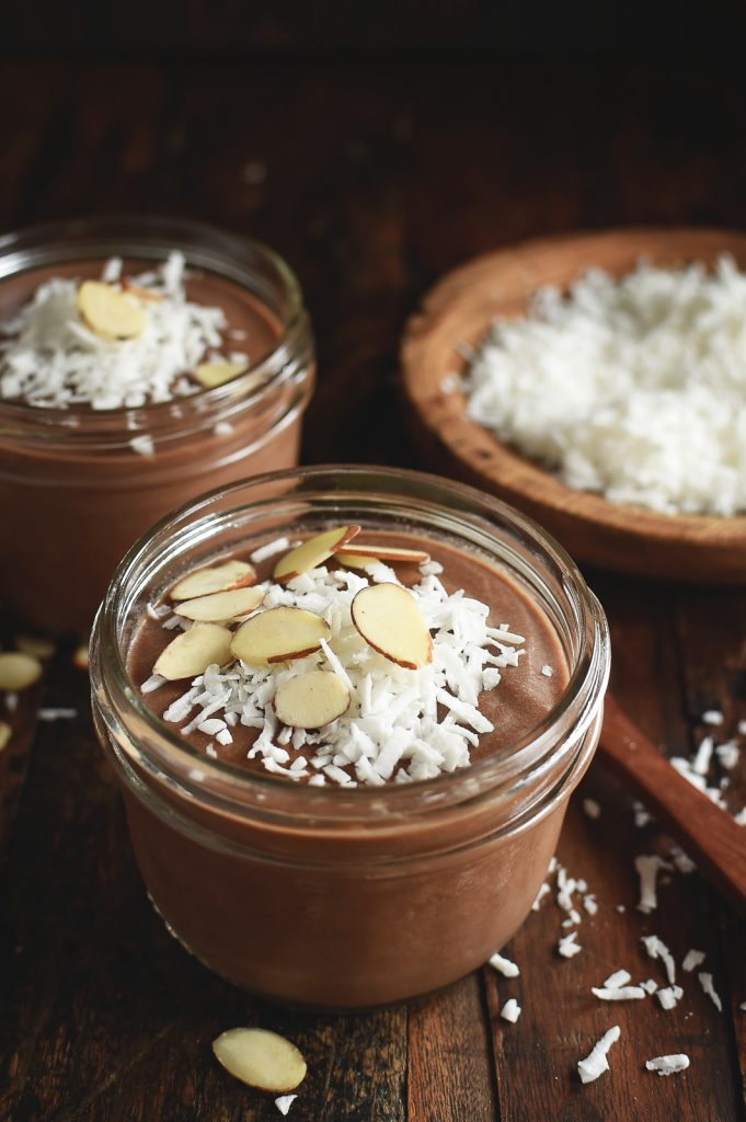 A vegan keto dessert of chocolate almond pudding in two glass jars with a bowl of coconut to the right on top of a rustic background.