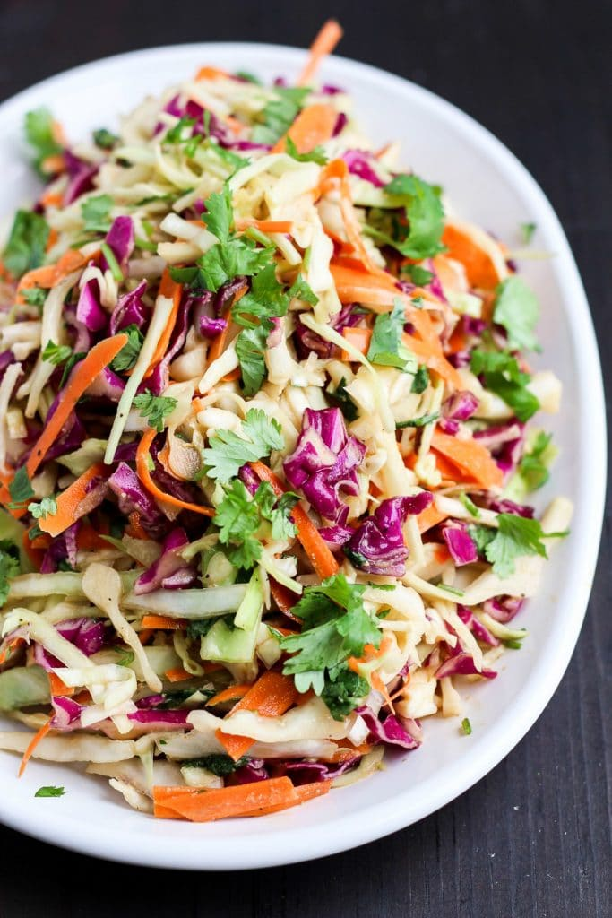 A vegan keto side dish of asian coleslaw is served on a large white platter and it's resting on a black background.