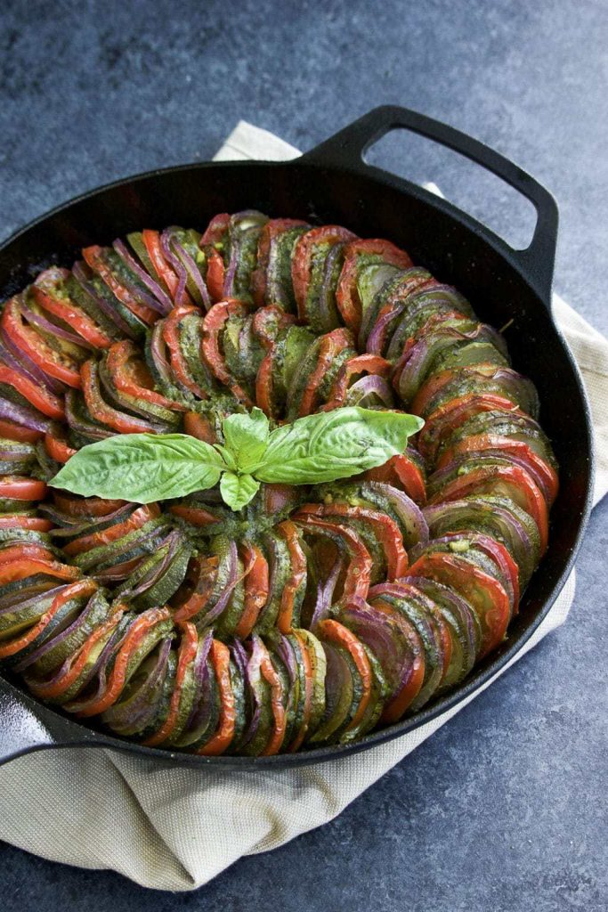 A cast iron skillet filled with thinly sliced zucchini, tomatoes, red onions, and pesto sauce resting on a nude towel with a blue background.