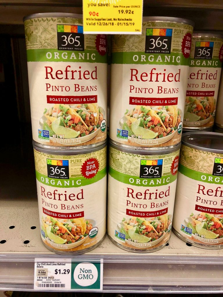 Multiple cans of organic refried beans on a shelf at Whole Foods.