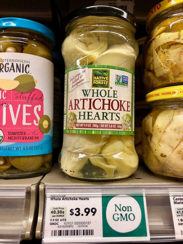 A jar of whole artichoke hearts on a shelf at Whole Foods.