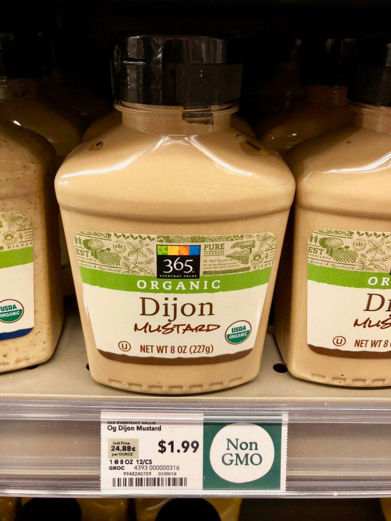 Multiple bottles of organic dijon mustard on a shelf at Whole Foods.