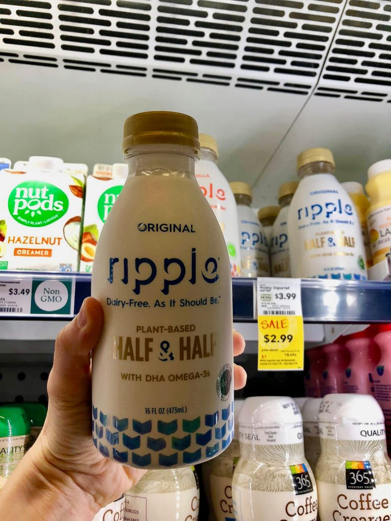 A hand holding a bottle of Ripple unsweetened half & half at Whole Foods.