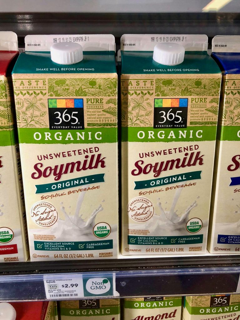 Two cartons of organic unsweetened soy milk on a shelf at Whole Foods.