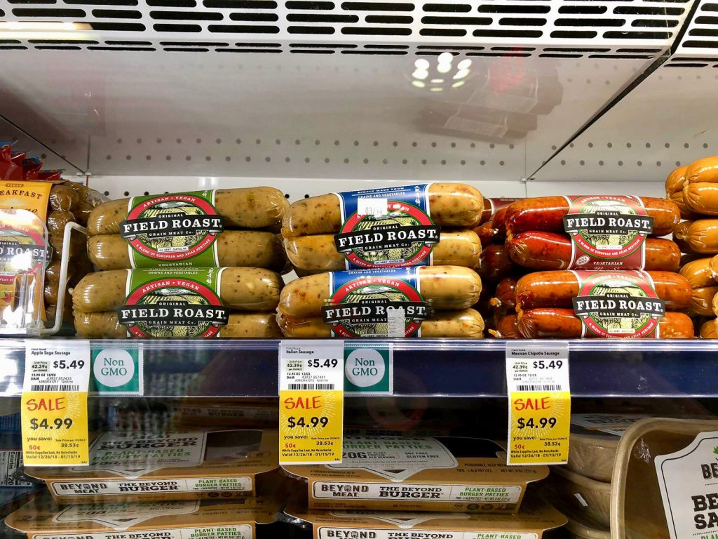 Multiple packages of Field Roast sausages on a shelf at Whole Foods.