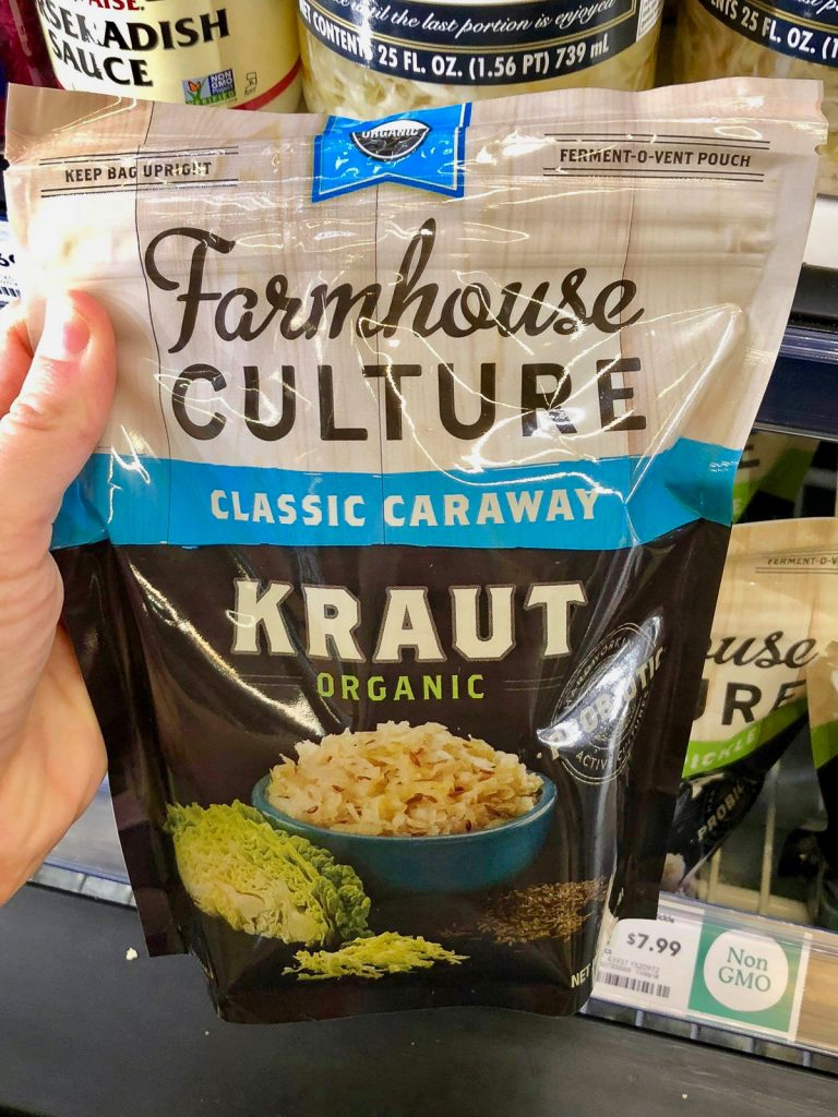A hand holding a bag of Farmhouse Culture sauerkraut at Whole Foods.