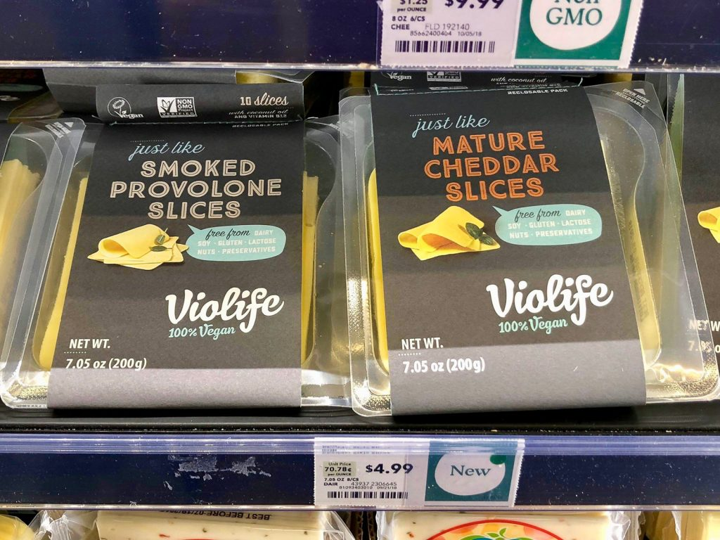 Two packages of Violife vegan cheese on a shelf at Whole Foods.