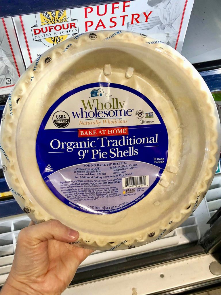 A hand holding a package of Wholly Wholesome vegan pie crusts at Whole Foods.