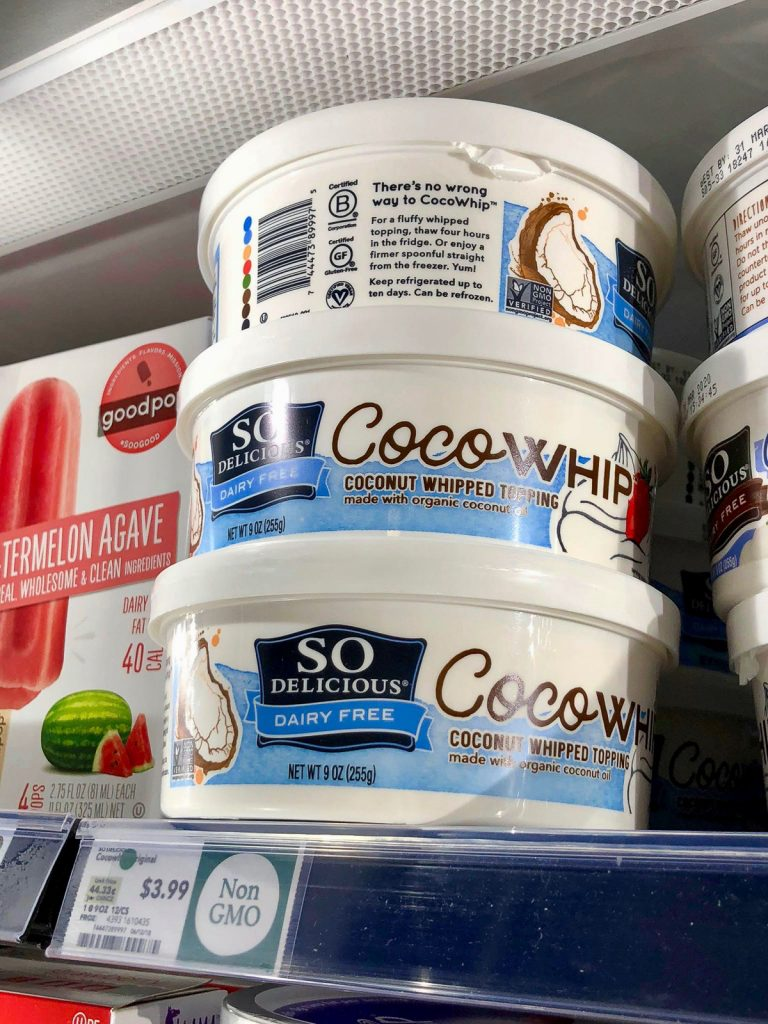 Three tubs of So Delicious vegan coco whip on a shelf at Whole Foods.