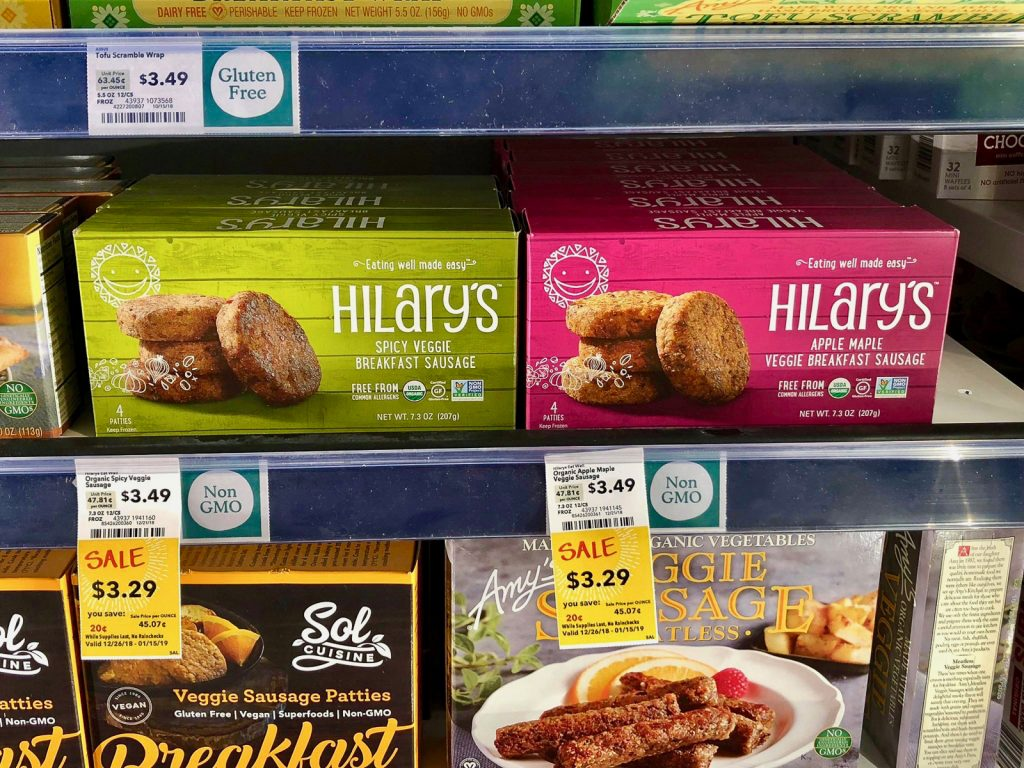 Multiple packages of Hilary's vegan products on a shelf at Whole Foods.