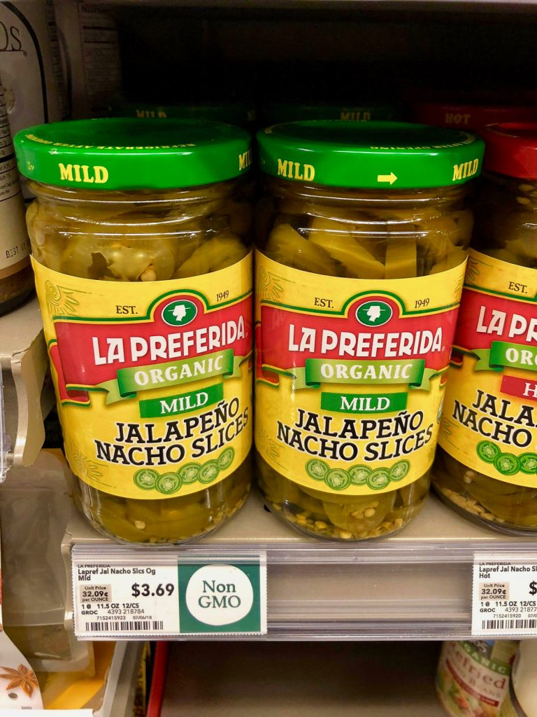 Two bottles of organic jalapeño slices on a shelf at Whole Foods.