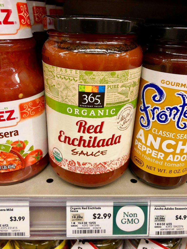 A jar of organic red enchilada sauce on a shelf at Whole Foods.