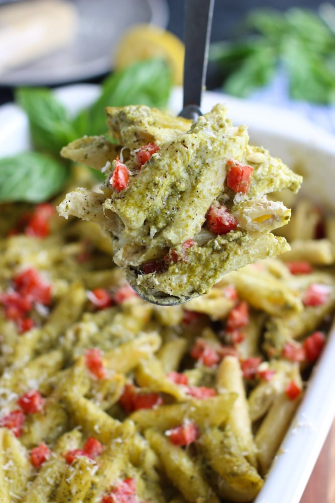 A spoonful of vegan pesto pasta casserole with tomatoes in a white dish.